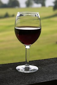 A glass of red wine is seen on a table.