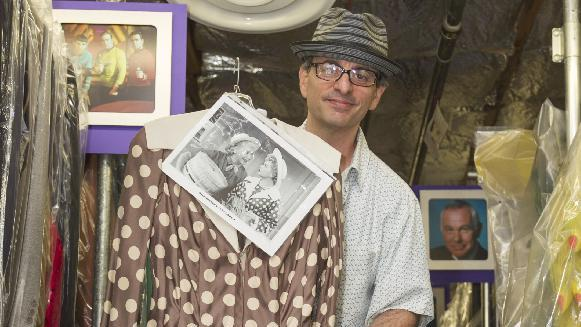 In this Friday, Nov. 30, 2012 photo, James Comisar shows a dress worn by Lucille Ball. The item is part of his television memorabilia collection in a temperature- and humidity-controlled warehouse in Los Angeles. (AP Photo/Damian Dovarganes)