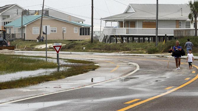 Residents carry belongings from the west end of the island as the roads are closed from 3-4 feet of sand covering the road in Dauphin Island, Ala. on Thursday, Aug. 30, 2012.  Isaac dumped as much as 4 feet of sand on roads on Dauphin Island, but damage isn't bad otherwise. Mayor Jeff Collier said Thursday no homes were destroyed on the coastal barrier, even at its vulnerable western end. Crews in tractors are moving sand off the streets. Collier says conditions may have been worse without a 3.5-mile-long sand pile that was built during the BP oil spill. He says the berm helped stop sand that would have wound up on streets and in sewers without it. (AP Photo/Butch Dill)