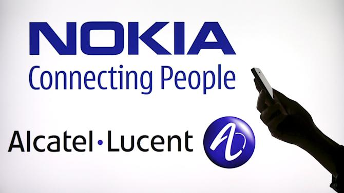 File photo illustration of a woman holding a smartphone in front of a screen displaying both Nokia and Alcatel Lucent logos in Paris