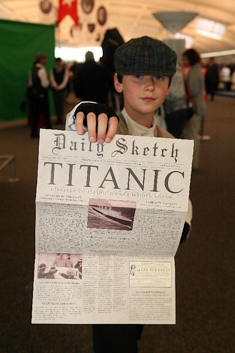 A child poses with a memorial newspaper in the departure lounge of the MS Balmoral cruise ship