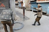 Indian police officers erect razor wire during a curfew in Srinagar, on February 9, 2013. Kashmiri separatist Mohammed Afzal Guru has been executed in New Delhi over his role in a deadly attack on the Indian parliament in 2001 -- triggering protests on both sides of the border in disputed Kashmir