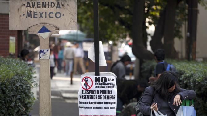 "A woman walks past a sign encouraging a ""no"" vote in an upcoming referendum regarding the installation of parking meters in the Condesa neighborhood of Mexico City, Friday, Jan. 18, 2013.  Many are vehemently opposed, saying the streets are public and no one should profit from them. But others hope the plan will cut down on cars from elsewhere. On Sunday, Condesa's residents will decide in a referendum whether they want the meters on their streets. (AP Photo/Eduardo Verdugo)"