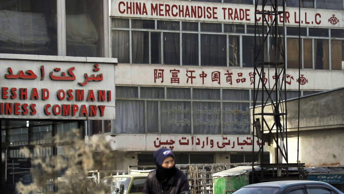 ADVANCE FOR SUNDAY JAN. 27 - In this Tuesday, Jan. 22, 2013 photo, An Afghan man rides his bike past a China Merchandise Trade Center in Kabul, Afghanistan. China, long a bystander to the bloody conflict in neighboring Afghanistan, is accelerating its involvement as U.S.-led forces prepare to withdraw, attracted by its vast, untapped mineral resources and concerned that post-2014 chaos could fuel its own Islamist insurgents. (AP Photo/Musadeq Sadeq)