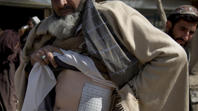 Habib Noor, shows a plaster on his body, from two U.S. Special forces and their Afghan translator named Zikrya who beat him he said, in Maidan Shahr, Wardak province, Afghanistan, Sunday, March 10, 2013. Afghan President Hamid Karzai, infuriated by villager reports of forced detentions and mass arrests, gave U.S. Special Forces two weeks to vacate Wardak province, located barely 30 kilometers (24 miles) from the Afghan capital of Kabul. The deadline for their withdrawal expired midnight Sunday, March 10, 2013. (AP Photo/Anja Niedringhaus)