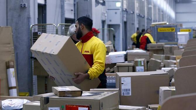 Worker load trucks with parcels at new distribution centre of German postal and logistics group Deutsche Post DHL in Berlin
