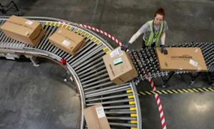 An Amazon employee sorts packages in Arizona: The online retailing giant's deep discounts may be problematic to its bottom line.