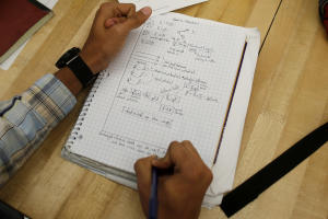 A student writes notes in the Advanced Placement (AP)…