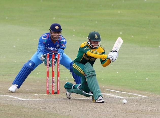 India's cricketer MS Dhoni (left) looks on as Quinton de Kock of South Africa bats during their one-day international in Durban on December 8, 2013