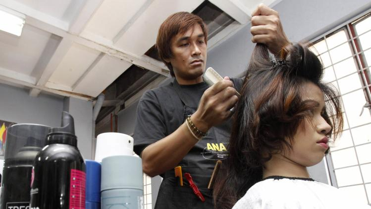 Edwin Manalo, 39 and married with 2 kids, works on the hair of a model inside the Ricky Reyes Learning Institute in Quiapo, metro Manila