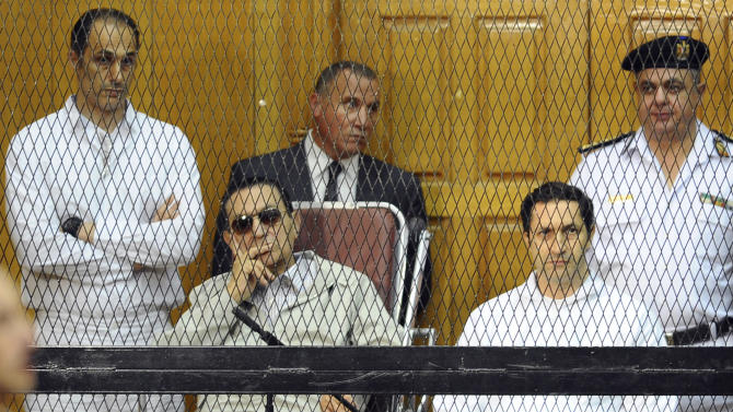 ALTERNATE CROP OF CAI103 -- Former Egyptian President Hosni Mubarak, seated, and his two sons, Gamal Mubarak, left, and Alaa Mubarak, right, attend a hearing in a courtroom at the Police Academy, Cairo, Egypt, Saturday, Sept. 14, 2013. Egypt's ousted long-time autocrat was back in court Saturday, grinning and waving for the resumption of his retrial on charges related to the killings of some 900 protesters during the 2011 uprising that led to his ouster. (AP Photo/Mohammed al-Law)