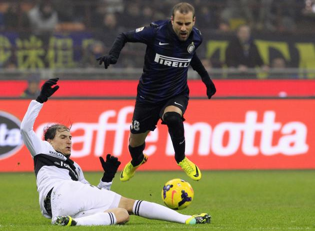 Inter Milan's Palacio is tackled by Parma's Paletta during their Italian Serie A soccer match at the San Siro stadium in Milan