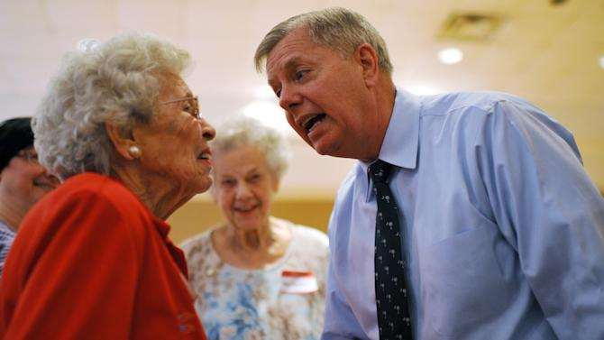 Sen. Lindsey Graham, right, speaks with Erminie Nave, left, after speaking at a campaign stop at American Legion Post 20 on Wednesday, April 23, 2014, in Greenwood, S.C. (AP Photo/Rainier Ehrhardt)
