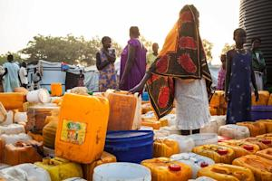 South Sudanese women stand among water containers at …