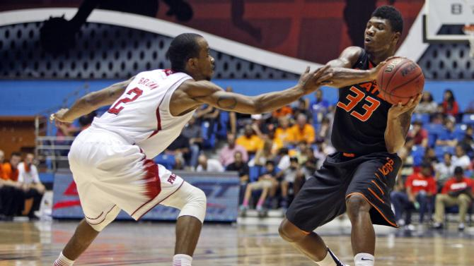NC State's Lorenzo Brown, left, pressures Oklahoma State's Marcus Smart during a NCAA college basketball game in Bayamon, Puerto Rico, Sunday, Nov. 18, 2012. (AP Photo/Ricardo Arduengo)