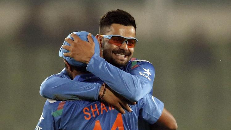 India's Virat Kohli, right, hugs teammate Mohammad Shami to congratulate on taking the catch to dismiss Sri Lanka's batsman Kusal Perera during their ICC Twenty20 Cricket World Cup warm up match in Dhaka, Bangladesh, Monday, March 17, 2014. (AP Photo/Aijaz Rahi)