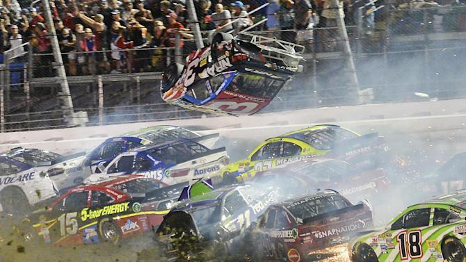 In this photo made early Monday, July 6, 2015, Austin Dillon (3) goes airborne as he was involved in a multi-car crash on the final lap of the NASCAR Sprint Cup series auto race at Daytona International Speedway in Daytona Beach, Fla. (AP Photo/Rob Sweeten)