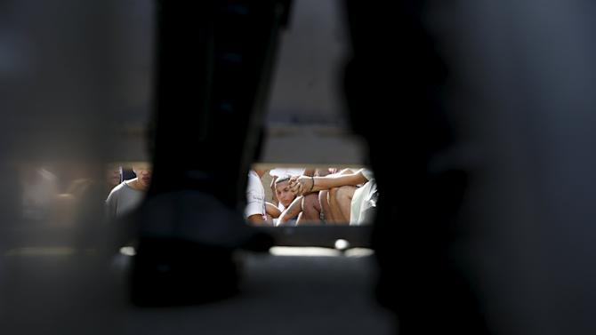 Inmates are seen sitting down, under a gate and through the legs of a police officer at the National Bolivarian Police prison, during a riot in Caracas, Venezuela
