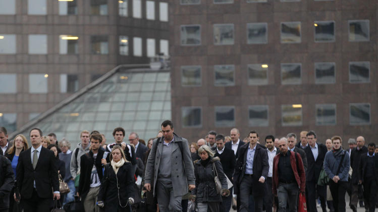Workers walk across London Bridge to their work places in the City of London, Thursday, Oct. 25, 2012.  Britain's economy emerged from its nine-month recession in the July to September quarter, when spending on the Olympics helped it grow by a bigger than expected 1 percent, according to official figures released Thursday. The number published by the Office for National Statistics beat the market consensus forecast of 0.6 percent growth and will make the Bank of England less likely to approve a further round of economic stimulus in November, analysts say.  (AP Photo/Sang Tan)