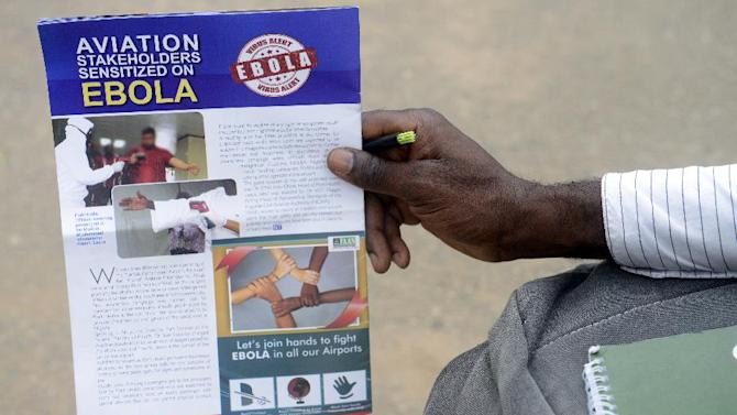 A worker holds a flyer on the Ebola virus at the Murtala Muhammed International Airport in Lagos on August 11, 2014