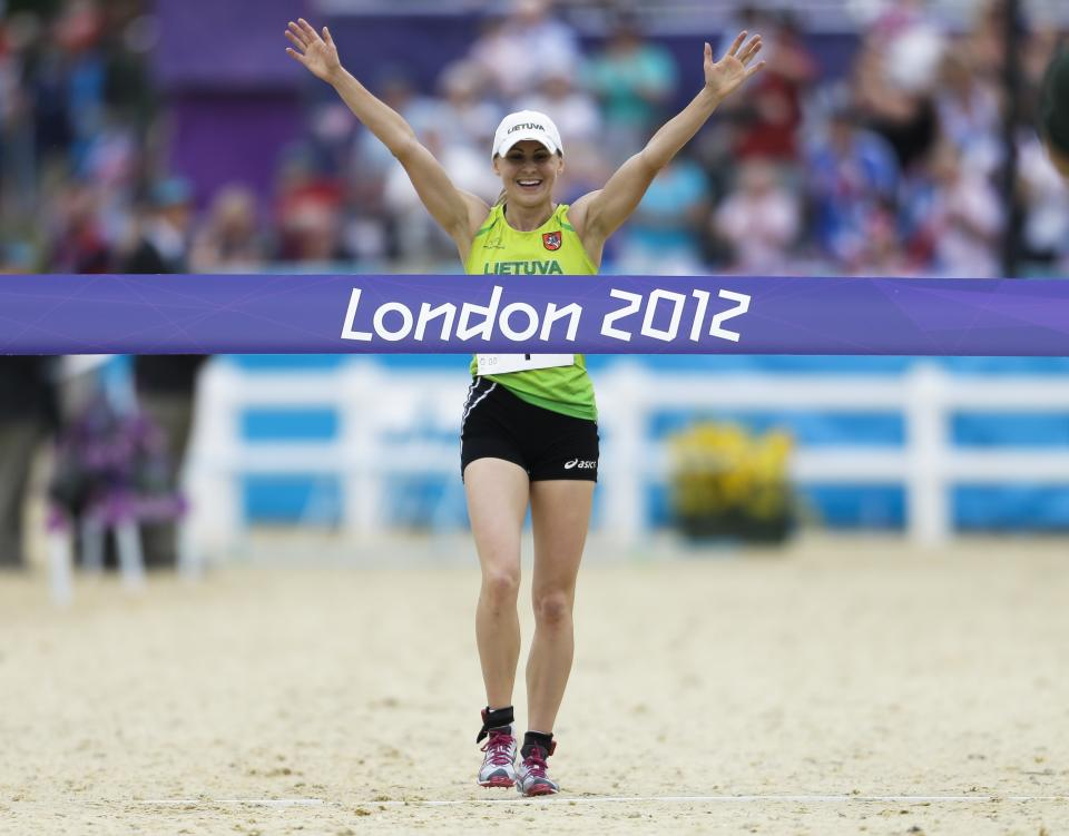 Laura Asadauskaite, of Lithuania crosses the finish line to win in the women's modern pentathlon, at the 2012 Summer Olympics, Sunday, Aug. 12, 2012, in London. (AP Photo/Markus Schreiber)