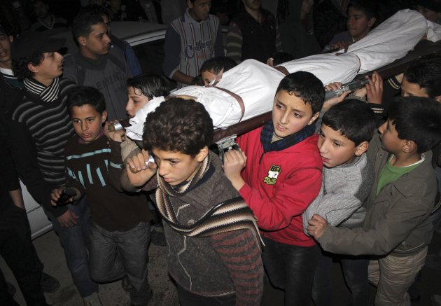 Children carry the body of a friend that was killed by shelling during heavy fighting between the Free Syrian Army and the forces of Syrian President Bashar al Assad in Jobar district of Damascus January 25, 2013. Picture taken January 25, 2013. REUTERS/Momahed Dimashkia (SYRIAPOLITICS - Tags: CONFLICT CIVIL UNREST TPX IMAGES OF THE DAY POLITICS)