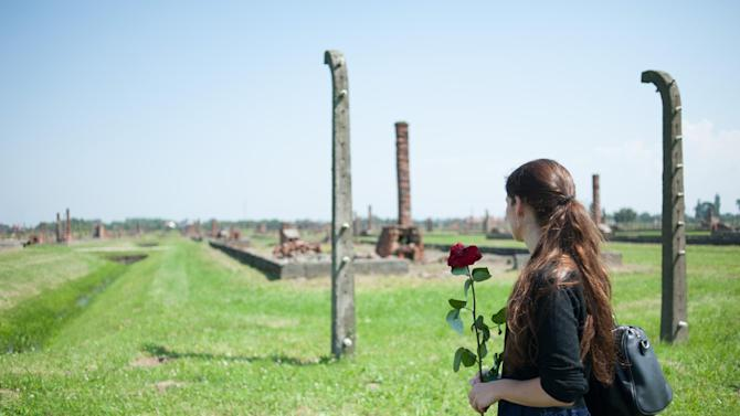 A woman holds a flower during the commemoration of the 70th anniversary of the the Roma Genocide in Auschwitz II-Birkenau, former Nazi concentration camp in Oswiecim on August 2, 2014
