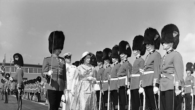 FILE In this June 29, 1959 photo, a member of the Royal Regiment of Canada towers over Queen Elizabeth II during review of guard of honor  in Toronto.  Decades have passed since Canadians replaced