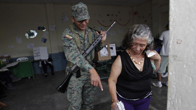 A soldier points the ballot box to a woman as she votes at a polling station in Quito, Ecuador, Sunday, Feb. 17,  2013. Ecuadoreans  elect president,  vice-president and National Assembly members Sunday with President Rafael Correa highly favored to win a second re-election.(AP Photo/Dolores Ochoa)