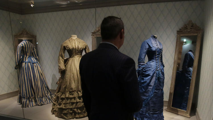 "A journalist looks at women's afternoon  dresses of the 19th century during the press day of the Impressionism and Fashion exhibition in at the Orsay museum in Paris, Friday, Sept. 21, 2012. To coincide with Paris Fashion week, a new and highly original exhibit  called ""Impressionism and Fashion"" opens at the Musee d'Orsay. It uses famous works of art to explore how at the dawn of impressionism, and as an emblem of ""modernite""  fashion, and how people dressed, became one of the main themes in art. The exhibition will open September 25, 2012 and last till January 2013. (AP Photo/Michel Euler)"
