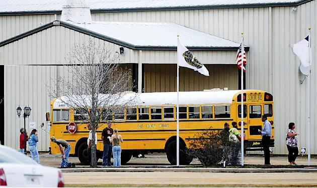 In this Tuesday, Jan 29, 2013 photo, residents look over the school bus where a shooting occurred near Destiny Church along U.S. 231, just north of Midland City, Ala. on Tuesday. Police, SWAT teams an