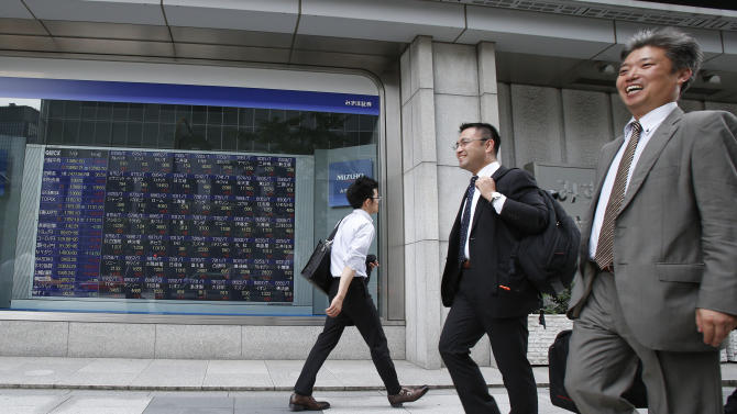 People walk by an electronic stock board of a securities firm in Tokyo Monday, July 1, 2013. Global stocks swung between gains and losses Monday after China's manufacturing weakened in June amid a credit crunch. Tokyo's Nikkei 225 rose 1.3 percent to 13,852.50. (AP Photo/Koji Sasahara)