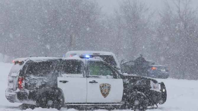A Lenexa Police vehicle stops to aid motorists stuck on a ramp to I-35 in Lenexa, Kan., Thursday, Feb. 21, 2013. The Kansas Turnpike Authority encouraged drivers to stay off the turnpike entirely; it runs from Oklahoma to Kansas City. There was virtually zero visibility on the turnpike early Thursday. And I-70 and other major highways in Kansas were snowpacked and icy, according to the Kansas Department of Transportation. Kansas Gov. Sam Brownback closed executive offices, except for essential personnel. He urged residents to have an extra cup of coffee, get out a board game and play with their children. (AP Photo/Orlin Wagner)