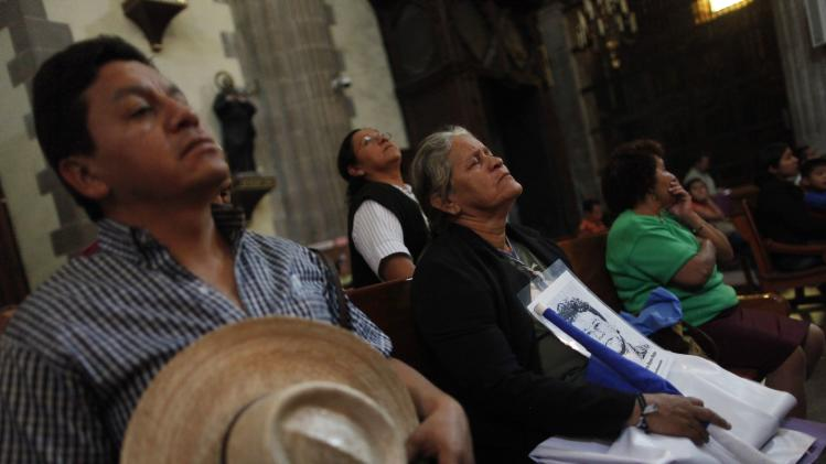"Women of the ""Caravana de Madres Centroamericanas"" (Caravan of Central American Mothers) pray next to a priest at the 0Metropolitan Cathedral in Mexico City"