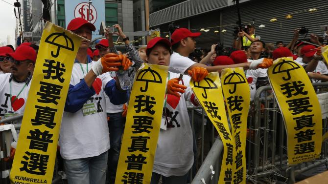 Workers representing bailiffs to clear a barricade under a court injunction take down protest banners at the main Nathan Road at Mongkok district in Hong Kong