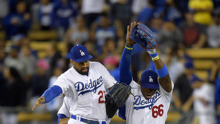 Los Angeles Dodgers' Matt Kemp, left, and Yasiel Puig, right, celebrate along with Scott Van Slyke after they defeated the San Diego Padres 2-1 in a baseball game, Thursday, July 10, 2014, in Los Angeles. (AP Photo/Mark J. Terrill)