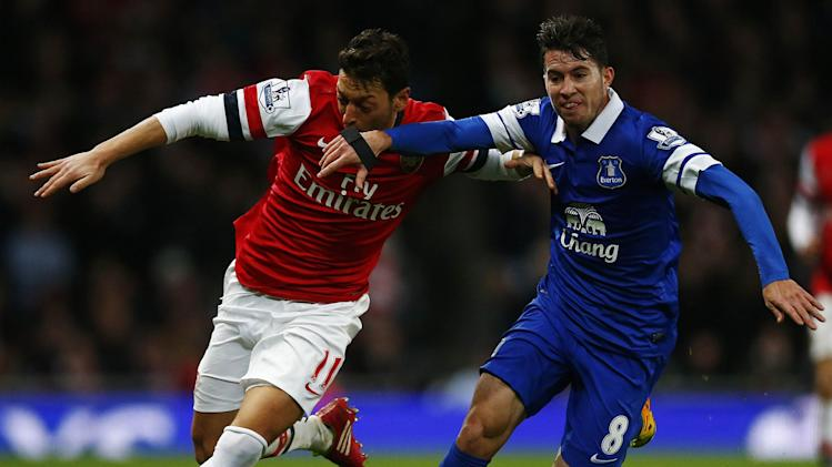 Everton's Oviedo challenges Arsenal's Ozil during their English Premier League soccer match at The Emirates in London