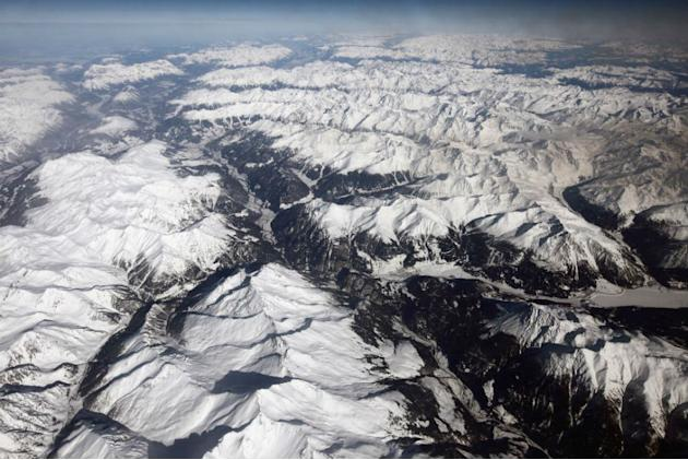 Snow covered alpine mountains seen from a commercial flight from Athens International Airport to Heathrow Airport.