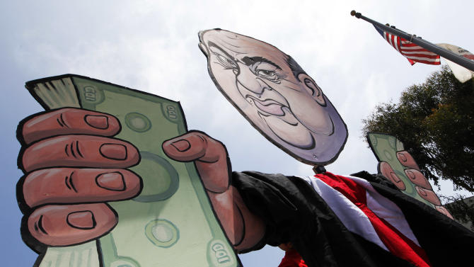 An unflattering caricature of Chancellor Charles B. Reed is seen at a demonstration and rally by the California Faculty Association outside a meeting of the Board of Regents of the California State University in Long Beach, Calif., Tuesday, May 8, 2012. Cal State trustees amended presidential compensation policy by freezing regents' salaries but to allow campus foundations to contribute to a president's salary, a proposal opposed by students and faculty. (AP Photo/Reed Saxon)