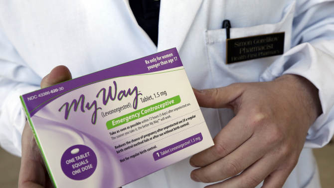 FILE - In this May 2, 2013 photo, pharmacist Simon Gorelikov holds a generic emergency contraceptive, also called the morning-after pill, at the Health First Pharmacy in Boston. The plaintiffs in a legal battle over emergency contraceptives say in a letter Wednesday June 12, 2013, the government has failed to comply with a New York judge's order to lift all restrictions on sales of the drug. (AP Photo/Elise Amendola, File)