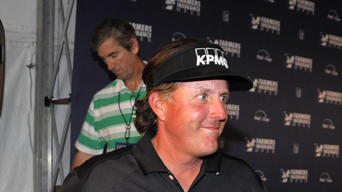 Golfer Phil Mickelson leaves a news conference after answering a questions about comments he made about taxes after his round in the pro-am at the Farmers Insurance Open golf tournament at Torrey Pines Wednesday, Jan 23, 2013, in San Diego.  (AP Photo/Denis Poroy)