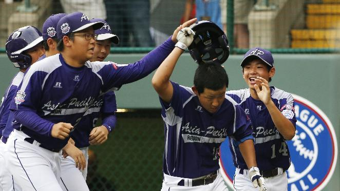 Seoul's Jae Yeong Hwang, center, is greeted by teammates after hitting a solo home run off Tokyo pitcher Suguru Kanamori in the sixth inning of a International semi-final baseball game against Tokyo at the Little League World Series tournament in South Williamsport, Pa., Wednesday, Aug. 21, 2013