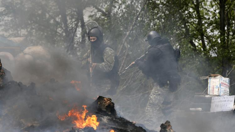 Ukrainian security force officers search a checkpoint set on fire and left by pro-Russian separatists near Slaviansk