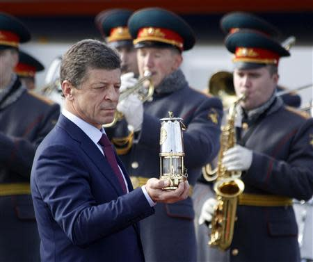 Russian Deputy PM Kozak holds the Olympic flame after landing in Moscow