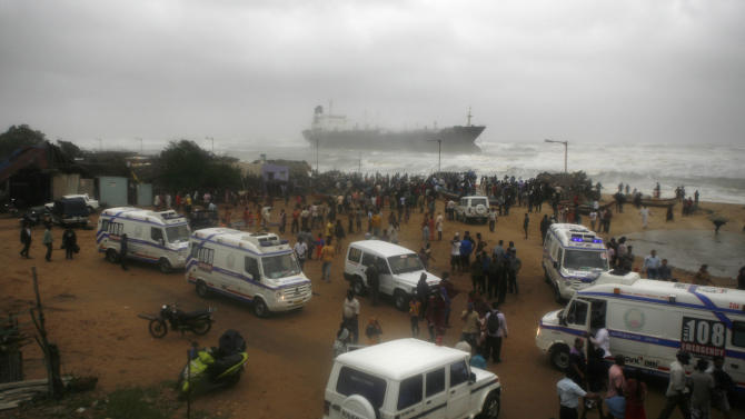 Ambulances stand on shore as people look at Indian ship Pratibha Cauvery that ran aground with people on board, reportedly due to strong winds on the Bay of Bengal coast in Chennai, India, Wednesday, Oct. 31, 2012. More than 100,000 people were evacuated from their homes Wednesday as a tropical storm hit southern India from the Bay of Bengal, officials said. Rain lashed the region and strong winds uprooted trees in some places. Weather officials said the storm packed winds of up to 100 kilometers (60 miles) per hour as it made landfall near Chennai, the capital of Tamil Nadu state. (AP Photo/Arun Sankar K)