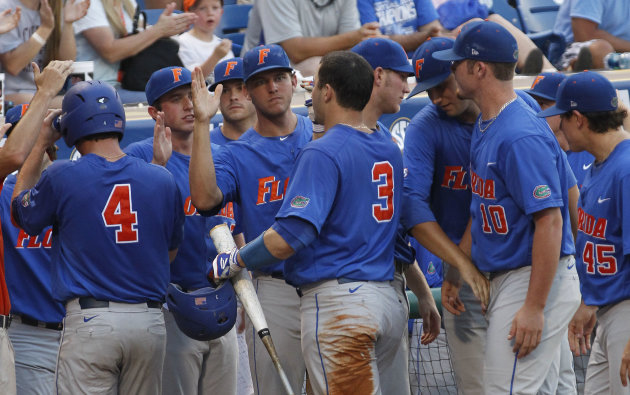 Florida players congratulate Mike Zunino (3) after he scored in the first inning of a NCAA college baseball game against South Carolina during the Southeastern Conference tournament in Hoover, Ala., Friday, May 25, 2012. (AP Photo/Dave Martin)