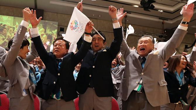 Japan's Prime Minister Shinzo Abe, center, Governor of Tokyo and Chairman of Tokyo 2020, Naoki Inose, second from left, and other members of the Japanese delegation celebrate as International Olympic Committee (IOC) President Jacques Rogge announces that Tokyo will host the 2020 Olympic Games during the 125th IOC session in Buenos Aires, Argentina, Saturday, Sept. 7, 2013. Tokyo defeated Istanbul in the final round of secret voting Saturday by the International Olympic Committee. Madrid was eliminated earlier after an initial tie with Istanbul. (AP Photo/Ian Watson, Pool)