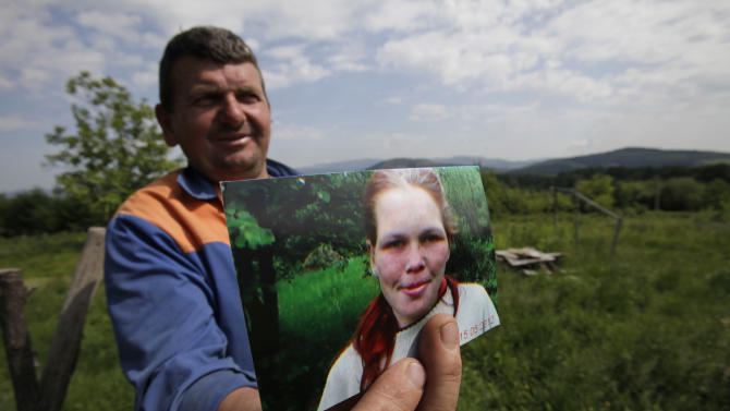 Sead Maklaic shows a photo of a German girl who was allegedly enslaved and abused by a Bosnian couple for years, in the village of Karavlasi, 140 kms north of Sarajevo, on Monday, May 28, 2012. A couple who allegedly beat a young woman while keeping her locked up for years have been arrested in Bosnia, an official said Sunday.  The 19-year-old girl was rescued after villagers tipped off authorities that she was being abused, the spokesman for the prosecutor's office in Tuzla, Admir Arnautovic, told The Associated Press. He said Milenko Marinkovic, 52, and his wife Slavojka, 45, were detained on suspicion of illegal imprisonment in a particularly cruel way. (AP Photo/Amel Emric)