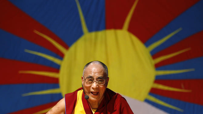 "FILE - In this Nov. 27, 2012 file photo, Tibetan spiritual leader the Dalai Lama laughs as he addresses Tibetan exiles living in Bangalore, in front of the Tibetan flag, in Bangalore, India. The Dalai Lama is set to headline India's Jaipur Literature Festival to speak about faith with one of his biographers, Pico Iyer. The Tibetan spiritual leader will hold a session on the festival's first day, Thursday, Jan. 24, 2013, titled: ""Kinships of Faiths: Finding the Middle Way."" (AP Photo/Aijaz Rahi, File)"