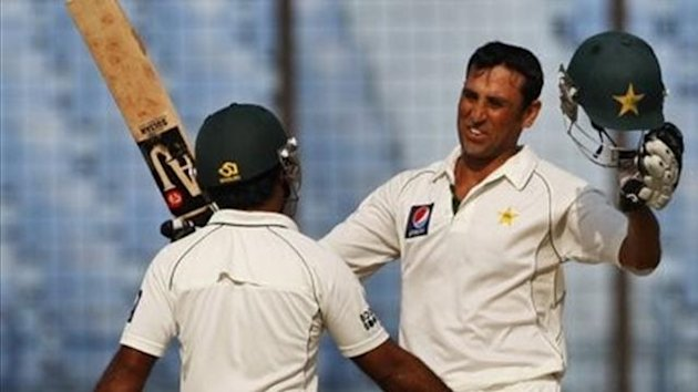 Pakistan's Younis Khan raises his bat after scoring a century as teammate Asad Shafiq greets him during third day of the first test cricket match against Bangladesh in Chittagong, Bangladesh, Sunday, Dec. 11, 2011.